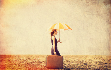 Redhead girl with umbrella and suitcase on raw field.