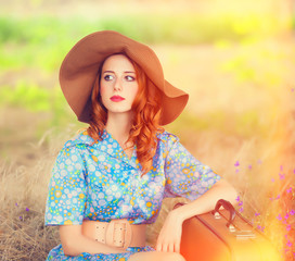 Redhead girl with suitcase sitting at autumn grass