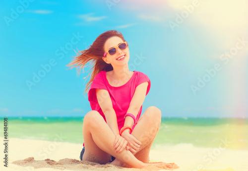 Leinwandbild Motiv Funny teen girl sitting on the sand at the beach.