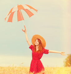 Redhead girl with umbrella at wheat field