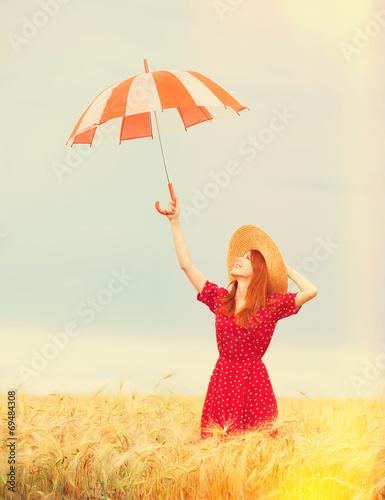 Leinwandbild Motiv Redhead girl with umbrella at wheat field