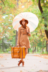 Redhead girl with umbrella and suitcase in the autumn park.