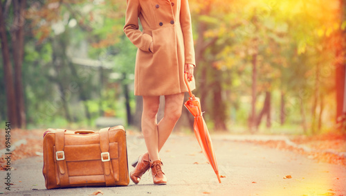 Leinwandbild Motiv Gril in coat with umbrella and suitcase in the park.