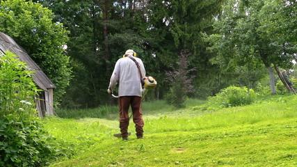 Gardener man cut grass with trimmer near rural house