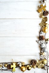 Gold and silver Christmas ornaments on white wooden background