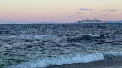 Cruise liner near to beach at sunset