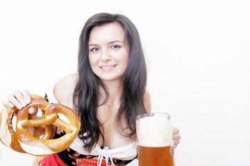 lächelnde Frau in Dirndl mit Brezn und Bierglas