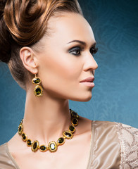 Young, beautiful and rich woman in jewels of gold