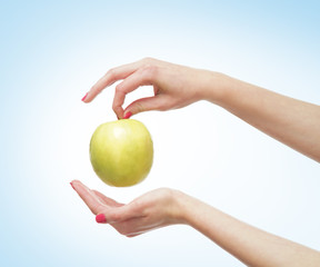 Beautiful female hands with an apple on light blue