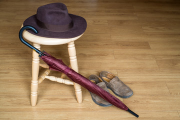 Umbrella, shoes and fedora hat on stool