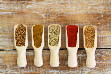 Indian spices on wooden scoops on wooden surface
