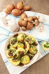 Young boiled potatoes with mushrooms on table, close up