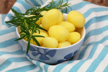 Baby potatoes with fresh rosemary in porcelain bowl, close up