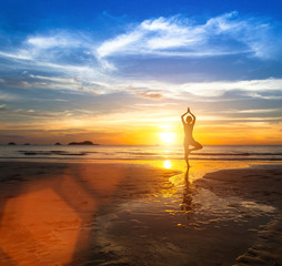 Silhouette of a beautiful yoga woman at sea sunset.