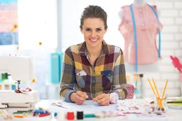 Portrait of happy dressmaker woman at work