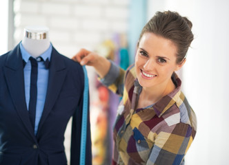 Tailor woman measuring business suit