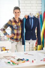 Portrait of tailor woman near mannequin wearing business suit