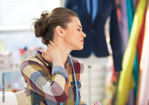 Portrait of tired tailor woman with neck pain - 69491733
