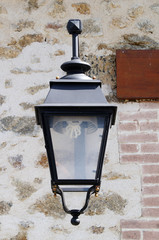 Lampadaire en métal sur une maison en pierre