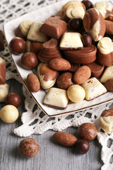 Different kinds of chocolates on plate on wooden table