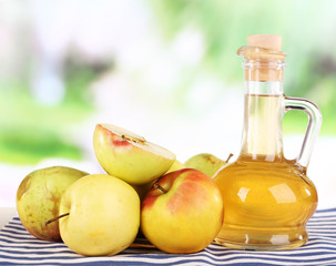 Apple cider vinegar in glass bottle and ripe fresh apples,