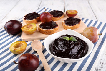Bowl of plum jam, slices of bread with plum jam and fresh plums