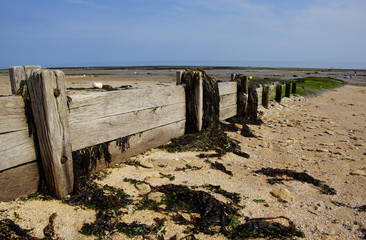 Holzwellenbrecher an der Küste der Normandie
