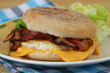 English muffin with fried egg, bacon and cheese