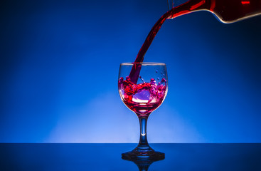 splash glass red wine blue background
