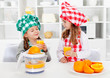 Little chef girls tasting the orange juice they made