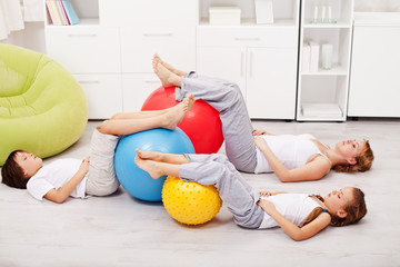 Relaxing after workout - woman and kids resting on the floor