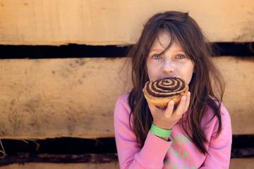 Mädchen sitzt auf einer Holzbank und isst eine Zimtschnecke