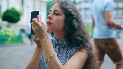 Woman using lip gloss and looking at oneself in the mirror