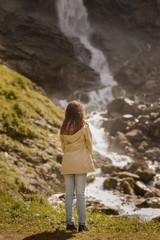 Rückansicht eines Mädchens vor einem Wasserfall