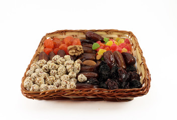 Fruit and nut dessert in a wicker basket. Isolated object on whi