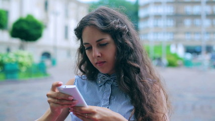 Woman sitting in the street cafe and using smartphone