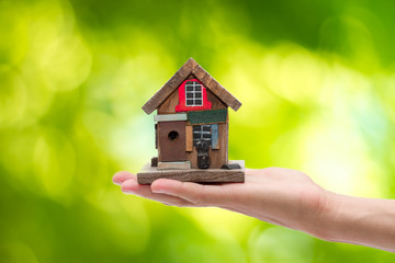 Closeup. Man's hand holding house isolated on white background