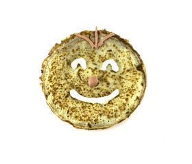 Painted a cheerful smiley pancakes. Isolated object on white bac