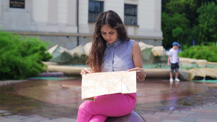 Woman sitting on the stone and reading map
