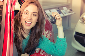 Young smiling woman holding key inside car