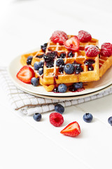 Golden waffles with berries on white table close up