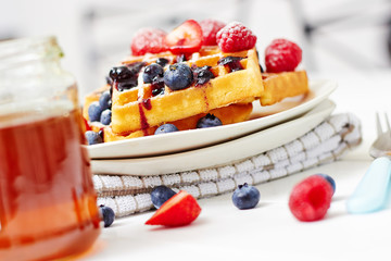 Golden waffles with berries and a jar of honey