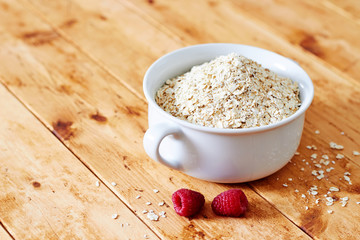 Raw oatmeal and raspberries on a wooden table wide view