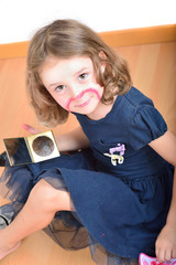 Little girl using make-up to turn herself into clown