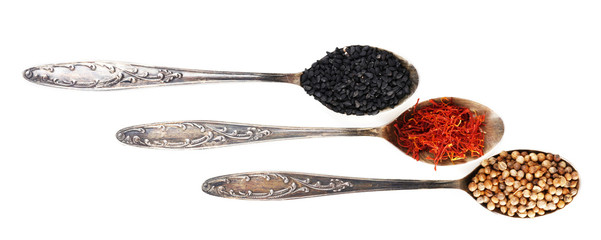 Spoons with herbal seasoning on white background isolated
