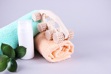Wooden roller brush, towels, mint and spray on grey background
