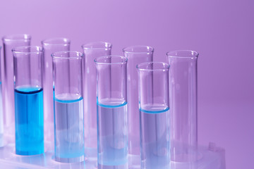 Test-tubes with blue liquid on purple background