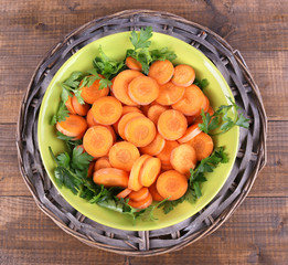 Slices of carrot, sorrel and parsley in green round bowl