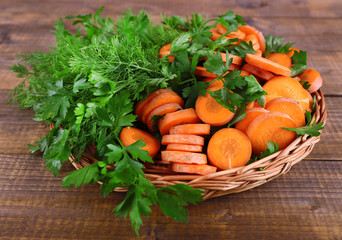 Slices of carrot and parsley in wicker bowl on wooden