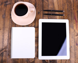 Tablet, cup of coffee, notebook and pens on wooden background